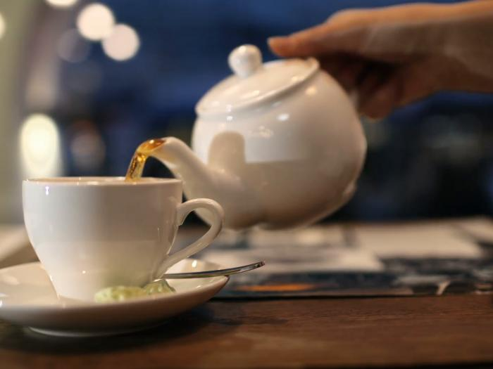 close-up-shot-of-female-hand-pouring-black-hot-tea-from-the-pot-into-the-cup_xk8fqbyb__F0000